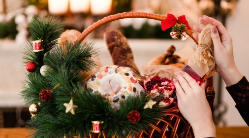 Woman hand arranging Christmas goods in a basket. Festive holiday food gift concept