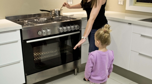 A woman teaching a child about oven safety
