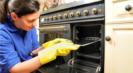 A ovenclean specialist putting an oven rack into the oven
