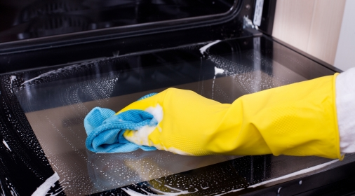 Woman cleaning oven with yellow glove