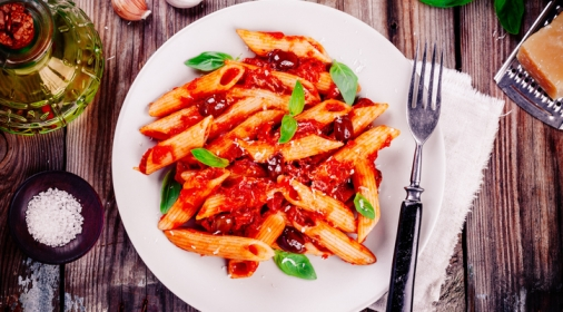 Italian penne pasta with tomato sauce, olives and basil