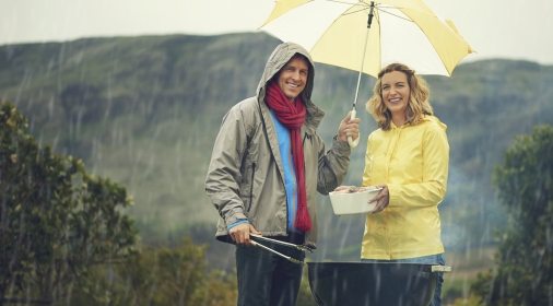 man and woman stood underneath and umbrella cooking on a BBQ