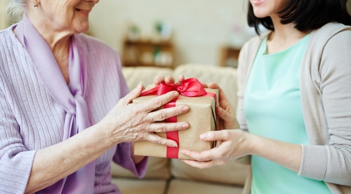 Young woman giving package with surprise to her mother
