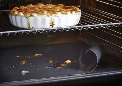 Inside of oven with pie cooking and non stick oven sheet