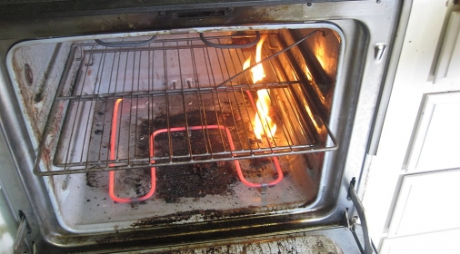 an oven on fire because it is dirty