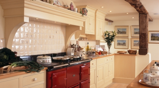 Red Aga oven in a cream country kitchen with large rustic wooden beam