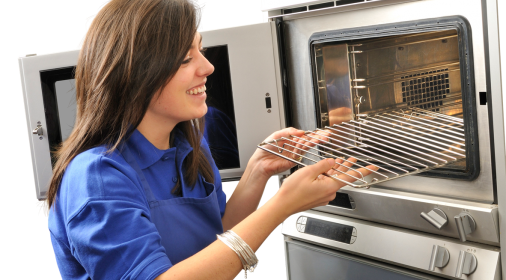 Ovenclean specialist putting oven rack in an oven