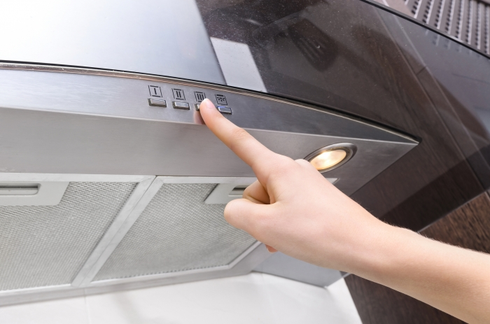 Cooker hood with someone pressing a button