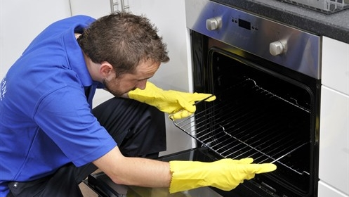 Ovenclean specialist putting an oven rack into the oven