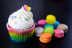 Colourful rainbow valentine cupcake with macaron.