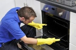 Ovenclean specialist putting oven rack into oven