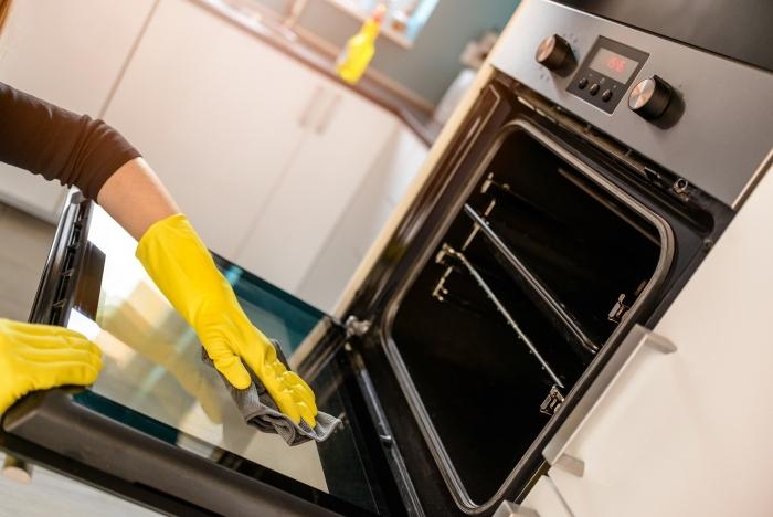 Woman cleaning an oven door