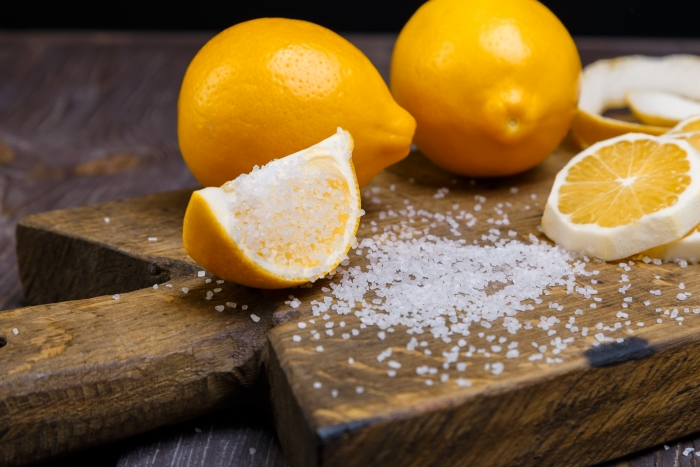 some sliced lemons on a wooden cutting board and sea salt