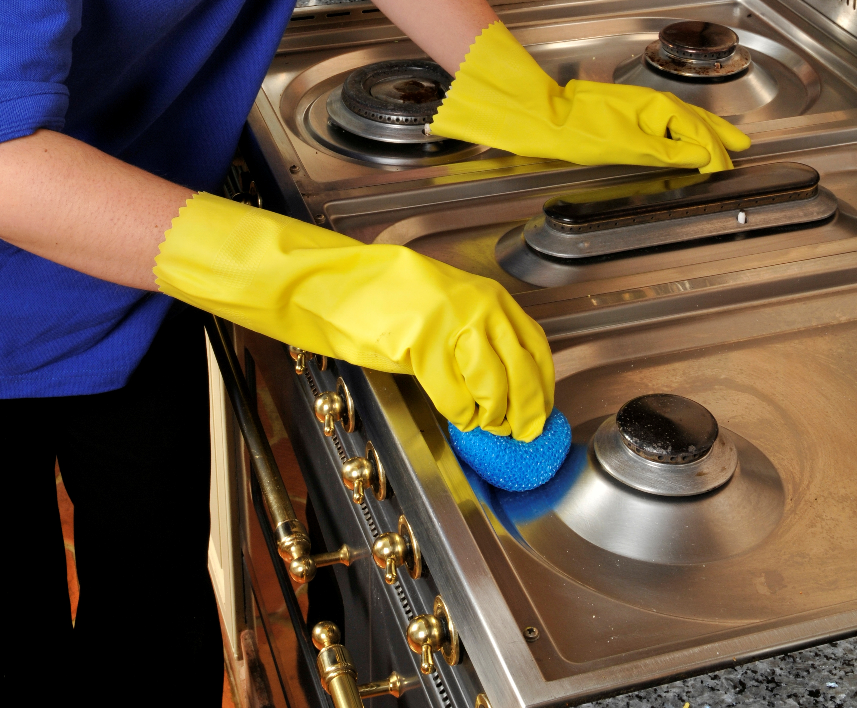 yellow rubber gloves cleaning an oven hob