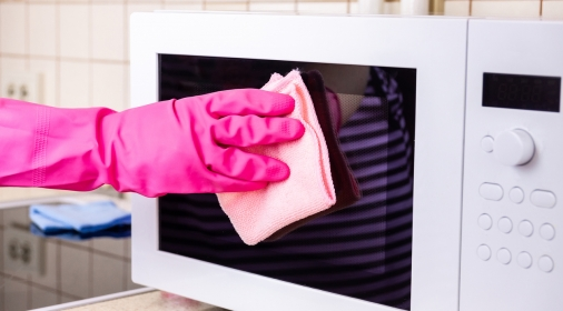 manual microwave cleaning with pink rubber glove