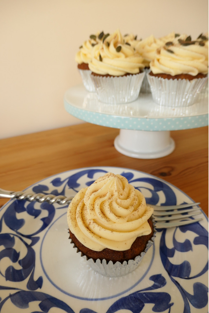 pumpkin cupcake with maple syrup buttercream on blue plate