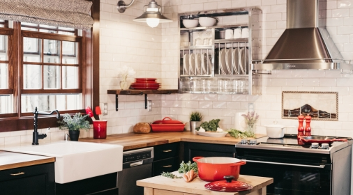 kitchen with black cupboards and red pots