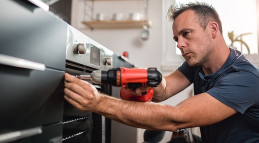Man building kitchen and using a cordless drill