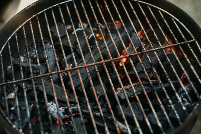A close-up of a rusty old barbeque grill with burning charcoal underneath it.