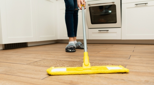 woman washes wooden floors from a laminate floor in a bright kitchen.