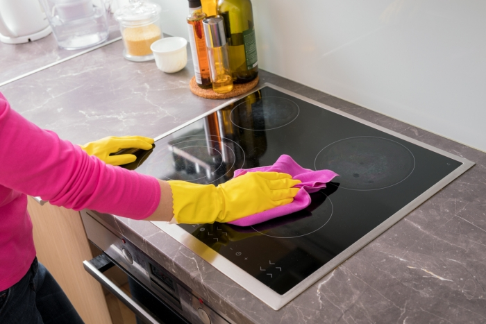 Person cleaning the induction hob in kitchen