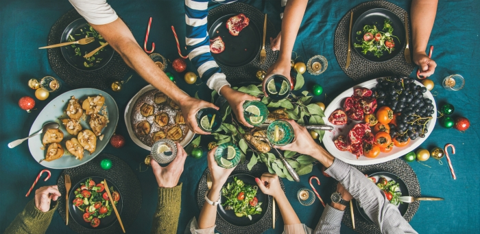 Company of friends of different ages or family gathering for Christmas or New Year party dinner at festive table. Flat-lay of human hands holding glasses with drinks, feasting and celebrating holiday together, top view.
