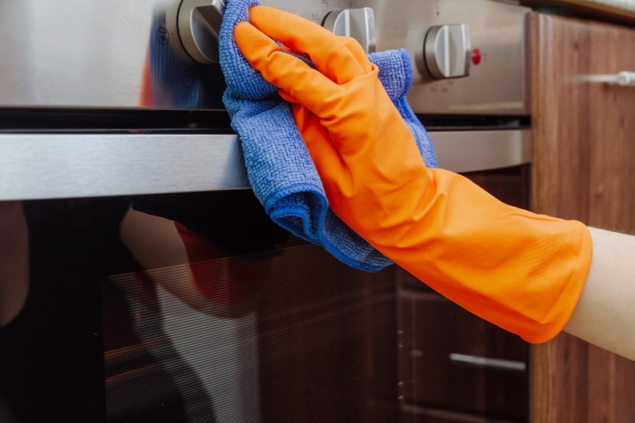 An orange-gloved hand with a microfiber cleaning cloth is being wiped on the outside of the electric oven. The cleaning of the kitchen concept
