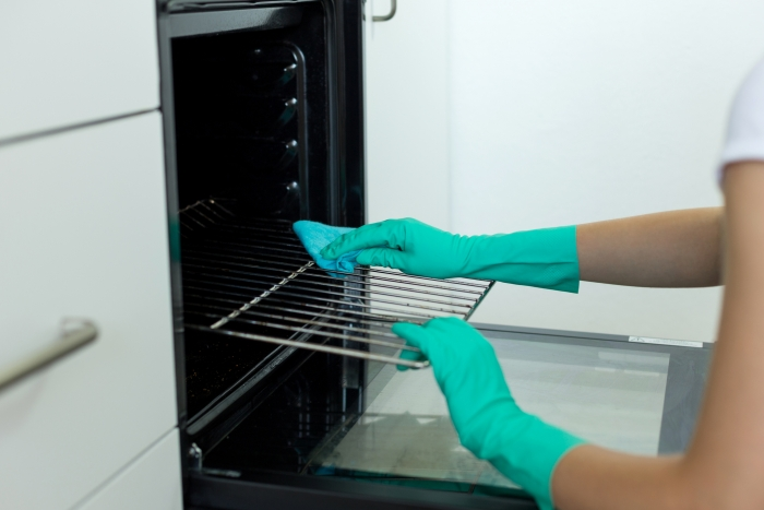 Woman hand in protective glove with rag cleaning oven