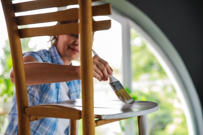 Cut out of a wooden chair that active mature woman is painting with white paint while learning a new hobbie during lockdown days at home.